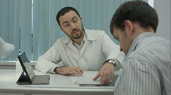 Male bearded doctor in clinic gives reccomendations to client Stock Footage