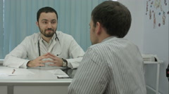 Male bearded doctor in clinic with male patient shake hands Stock Footage