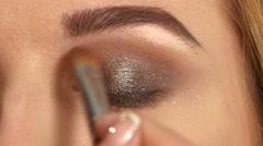 Stock Video Footage of Beautiful model applying eyeliner closeup on eye, Close up
