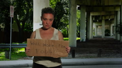 Homeless woman Standing Under An Overpass Holding A Sign Stock Footage