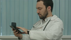 Serious male doctor focus on calculation of costs and revenues Stock Footage