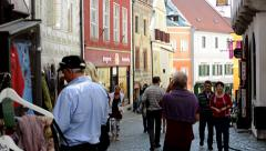 View of the historical street with shops - many people walk  Stock Footage