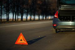Stock Photo of Warning triangle with a broken down car