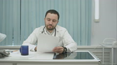 Tired  from work, bearded doctor drink from cup and continue woking with Stock Footage