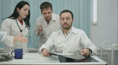 Laughing doctors studying X-ray Stock Footage