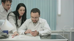 Two physicians in good mood discussing something in internet at medical center Stock Footage