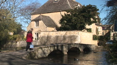 Old couple walking over bridge Cotswolds England Stock Footage