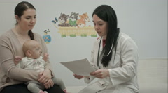 Female pediatrician doctor shows some papers to woman with small baby Stock Footage