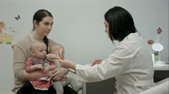 Cute newborn twins being examine by pediatrician with toy Stock Footage