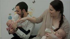 Happy young parents feed newborn twins from a bottle - stock footage
