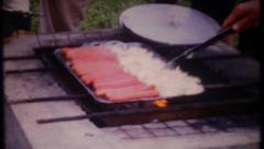 3008 hot dogs & onions on the grill at family picnic - vintage film home movie Stock Footage