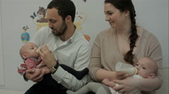 Young couple feed newborn twins from a bottle Stock Footage