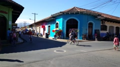 Street scene with people, traffic and colorful houses in Granada Stock Footage