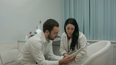 Two physicians in good mood analyze results of patient to diagnose disease, then Stock Footage