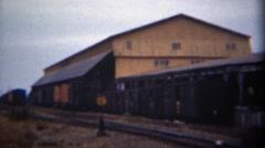 1949: Industrial warehouse lumber mill train yard rail line loading center.  - stock footage