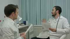 Bearded doctor shows new drugs to intern - stock footage