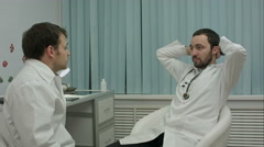 Two doctors relaxing at modern hospital indoors, speaking about life and work Arkistovideo