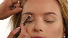 Beautiful woman draw beauty shape of eyebrows using cosmetic brush. Close up Stock Footage