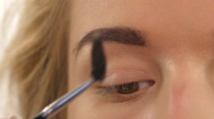 Stock Video Footage of a beautiful young woman comb her eyebrow. Close up. Slow motion