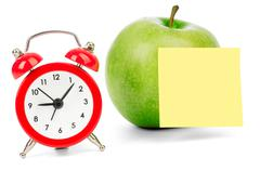 Fresh apple with alarm clock and sticker - stock photo