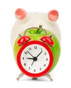 Fresh green apple with alarm clock and piggy bank Stock Photos