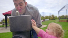 Dad waits for daughter to press the drinking fountain button - stock footage