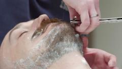 Shaving the beard in the Barber shop. Left angle. Medium Shot Stock Footage