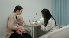 Pediatrician doctor at medical cabinet gives recommendations to mother with Stock Footage