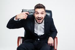 Crazy hysterical businessman sitting and put gun to his temple Kuvituskuvat