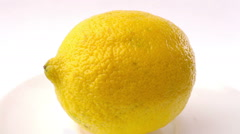 Yellow lemon turning on itself on a white background Stock Footage