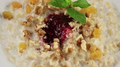 Stock Video Footage of Healthy breakfast, oatmeal porridge, raisins, walnuts and milk (loop)