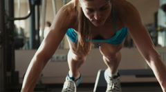 The woman in sportswear does push-ups in a gym Stock Footage