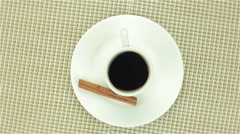 Cup of coffee with cinnamon on colour napkin - stock footage