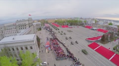 Military motorcade moves along square with many people on tribunes - stock footage