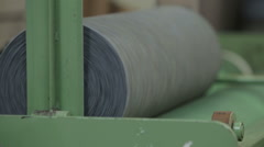 Harris tweed fabric being processed and rolled up in a local mill - stock footage