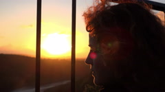 Woman searching of freedom behind the bars at sunset Stock Footage
