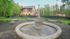 Fountain and several residential houses among forest at summer Stock Footage