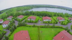 Several cottages on lake shore at summer cloudy day. Aerial view Stock Footage