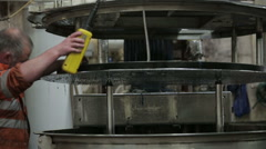 Worker in a mill dyeing wool in a large container - stock footage
