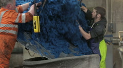 Worker in a mill removing dye'd wool from a large container - stock footage