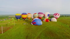 Group of colourful air balloons on grass field before fly Stock Footage