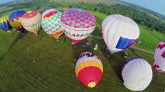 Several of colorful air balloons on grass field before fly at summer Stock Footage