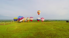 Grass field with colourful air balloons which begin fly at summer Stock Footage