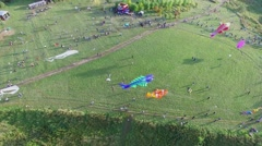Crowd of people launch kites on grass field at summer Stock Footage