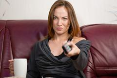 Sad irritated young woman using tv remote control at home - stock photo