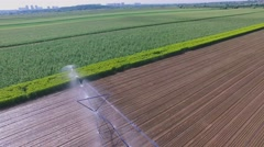 Tractor moves watering system across farm field at summer Stock Footage
