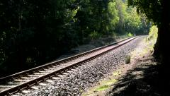 View of the railway in nature surrounded by trees and bushes - sunny day  Stock Footage