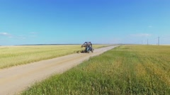 Tractor ride by sandy road across rue field at summer sunny day. Stock Footage