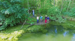 Family fishing on pond among trees at summer sunny day. Aerial view Stock Footage