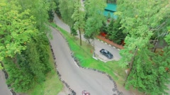 Two carts ride by racing track among trees at summer day. Stock Footage